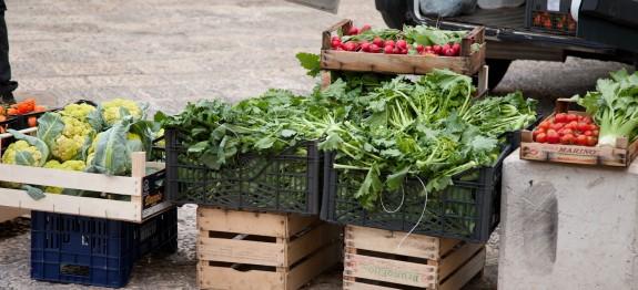 Italian farmer selling produce on street corner.